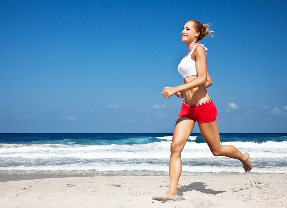 Healthy woman running on the beach, doin