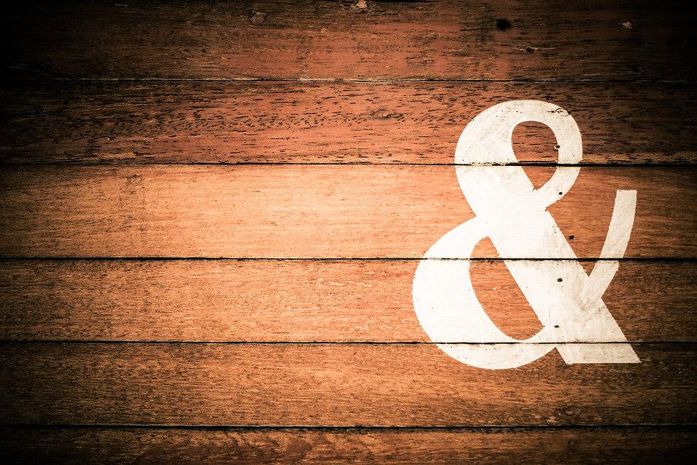 ampersand & sign painted on wooden backg