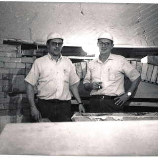Two men rebuilding the glass furnace.