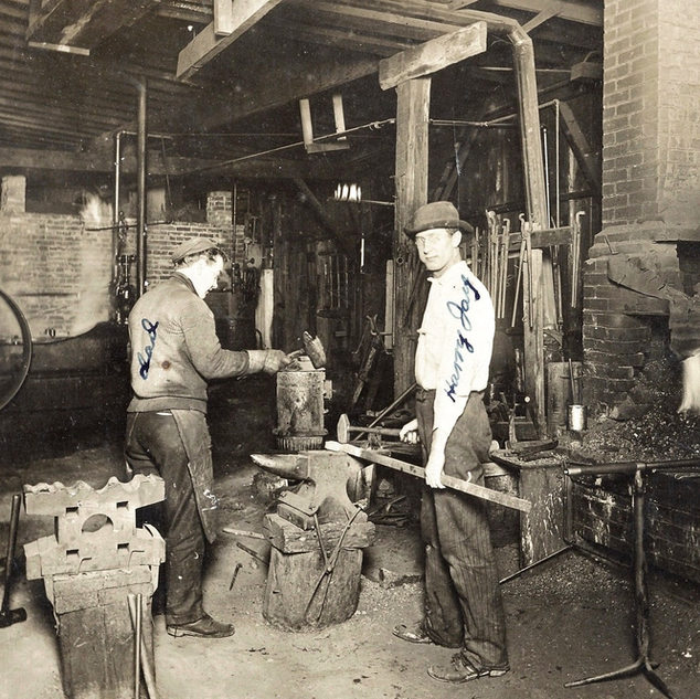 Blacksmith shop at West Fork glass.  Note blow pipes to the right to be repaired.