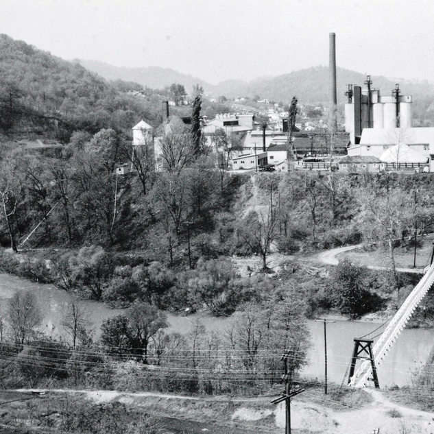 Rolland and the West Fork river with swinging bridge between the two plants.