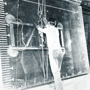 """A glass cutter places a large sheet of 3/16"""" thick, known as heavy strength on a tilt cutting table to be cut into a smaller size."""