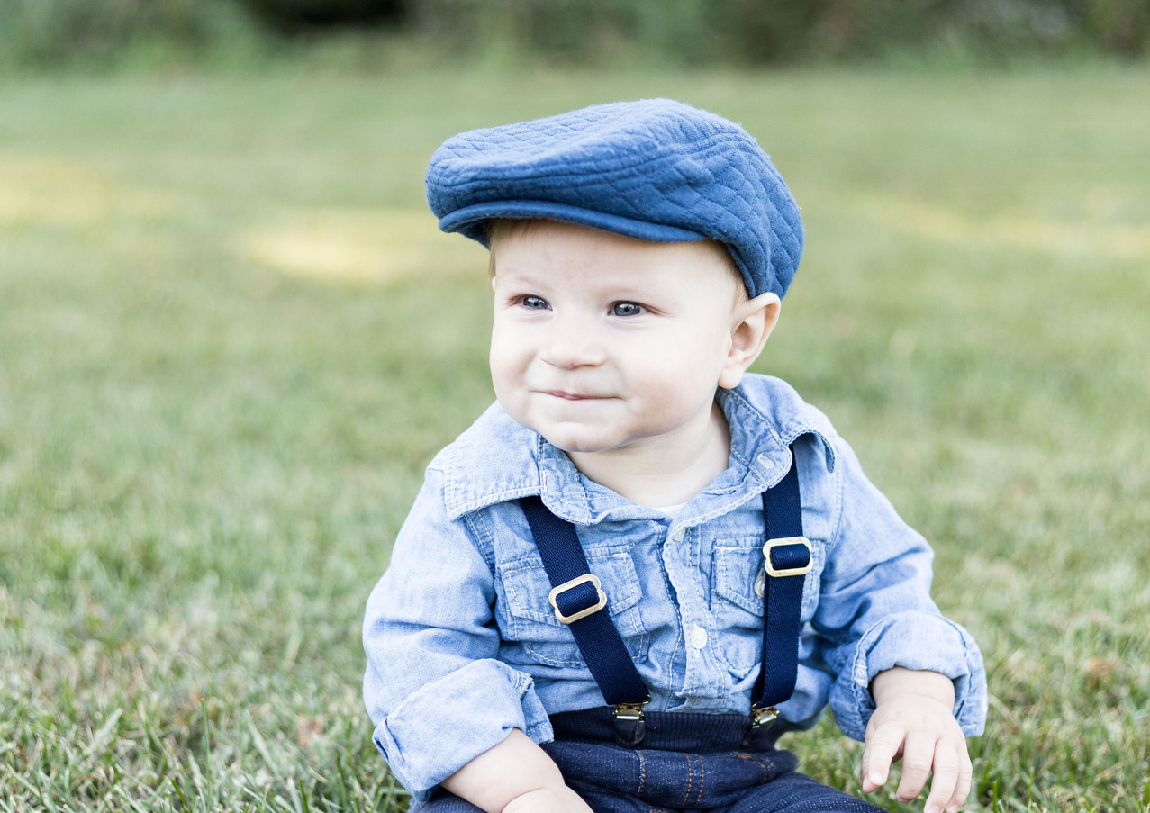 9 month old boy in blue hat and suspende