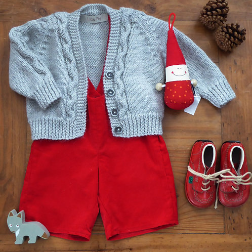 Handmade grey knitted baby cardigan with cable details and red bib shorts