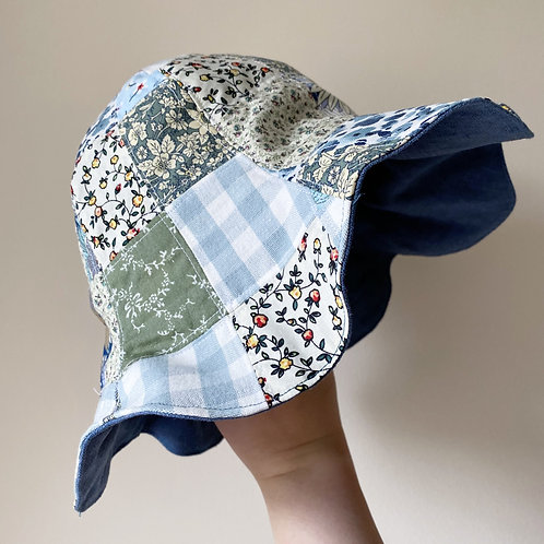 Floral side of handmade blue reversible floral patchwork sun hat with scallop petal edge cotton and linen by little fig