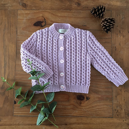 Handmade pink baby cardigan in a vintage style with cable detail