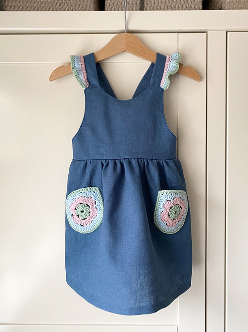 Navy blue linen children's pinafore dress with crochet frill straps and crochet flower pockets by Little Fig