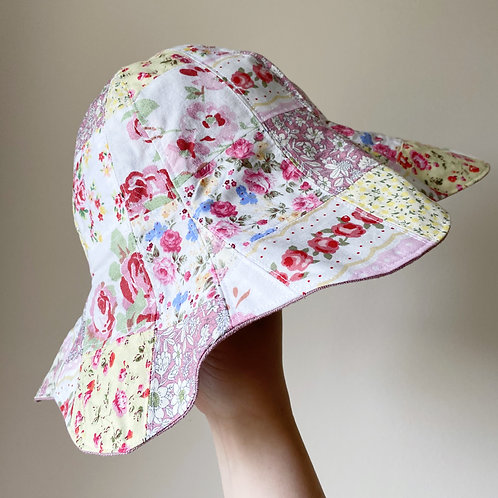 Floral side of handmade pink reversible floral patchwork sun hat with scallop petal edge cotton and linen by little fig