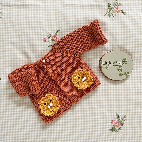 Orange knitted raglan sleeve baby cardigan with yellow lion motif pockets by Little Fig