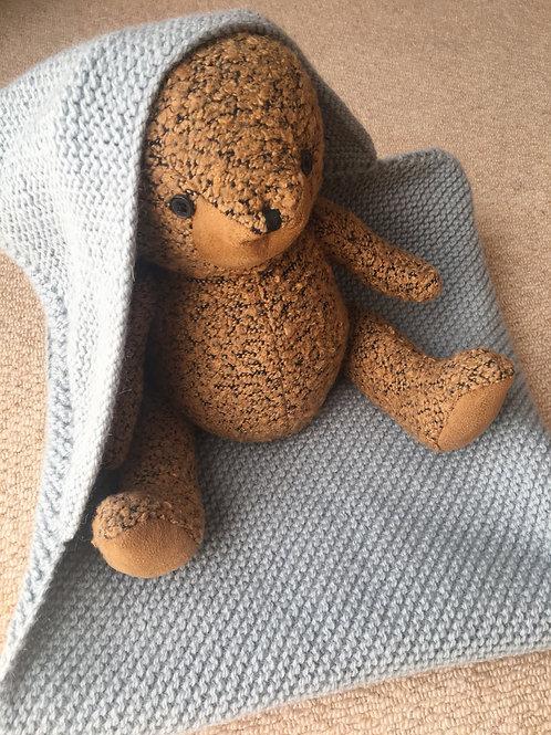 Teddy bear wearing a blue hooded knit blanket