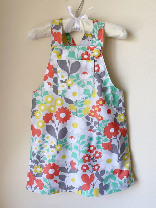 Handmade Bobbie dungaree pinafore dress with hand covered buttons in big floral print by Little Fig