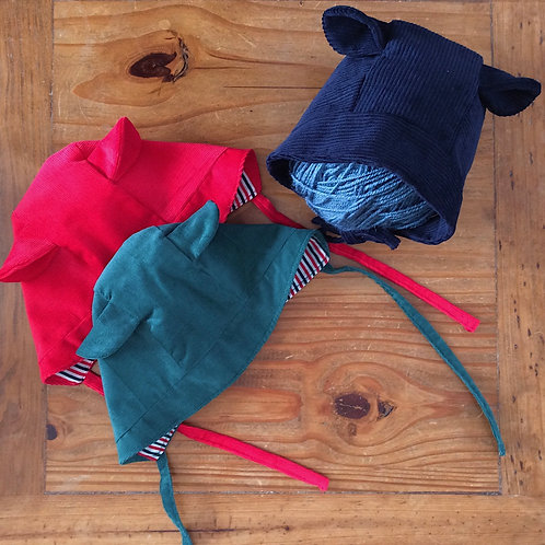 Children's corduroy bonnet in red, bottle green and navy blue, with bear ears and straps to tie by Little Fig