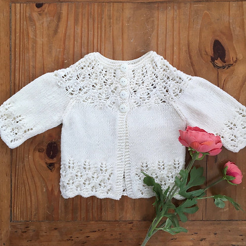 White knitted baby cardigan with a lacy stitch on the yoke