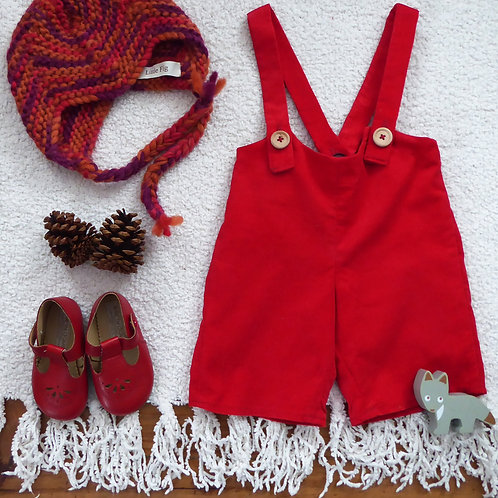 Red corduroy bib shorts with a red knitted aviator hat