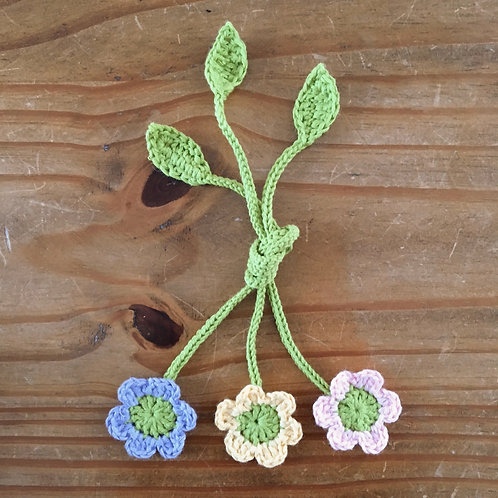 Three handmade crochet umbilical cord ties with flowers and leaf motifs in purple yellow and pink