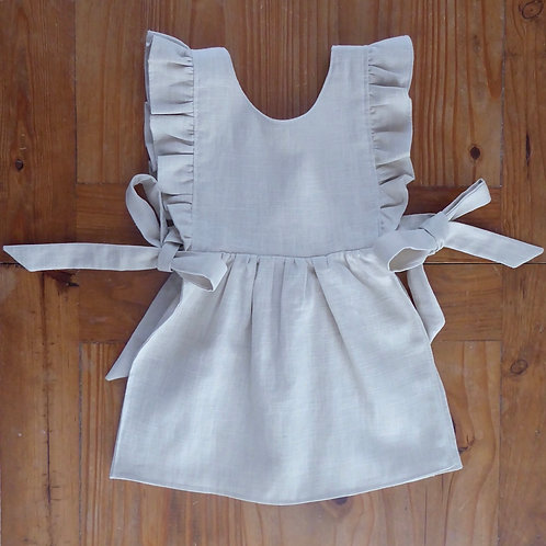 Dorothy beige linen children's pinafore with ruffle and bow tie detail by Little Fig