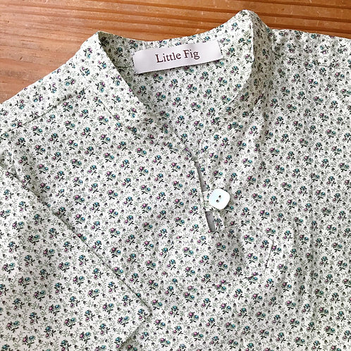 Close up of floral smock style baby top with button fastening at neck
