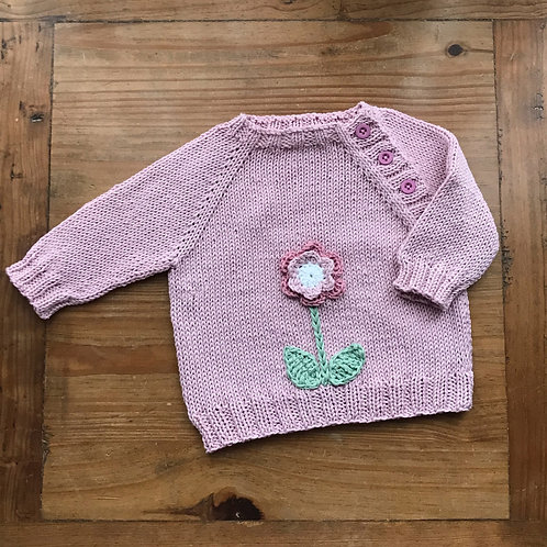 Pink flower knitted baby jumper with crochet flower