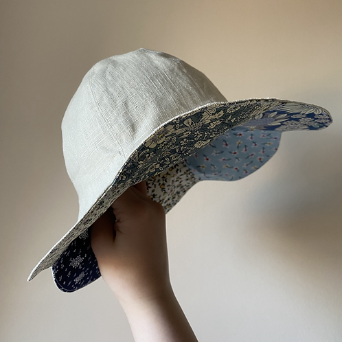 Handmade petal patchwork linen and cotton reversible sun hat in blue by little fig