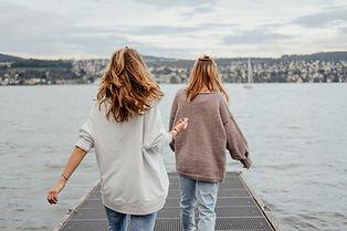 Lykkelige kvinder gående ved havet