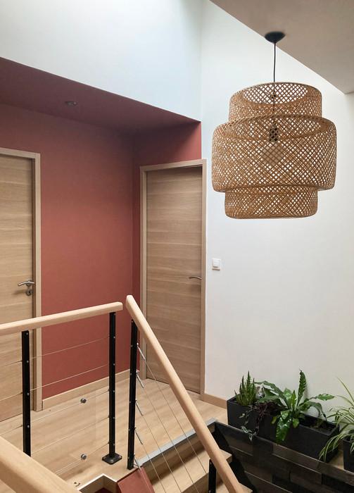 Couloir à l'étage conçu et décoré avec un peinture terracota et s'association harmonieusement avec une suspension lumineuse en rotin