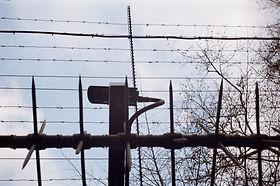 A surveillance camera behind barbed wire.