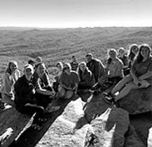 College students sitting on a rock overlooking mountains
