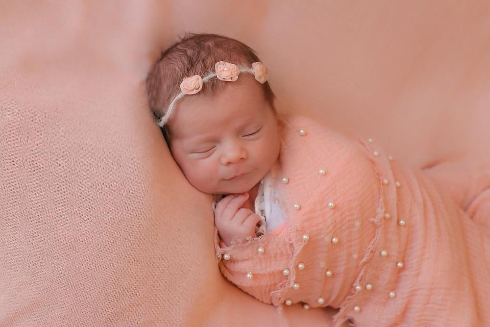 newborn girl in pink sleeping on pink blanket