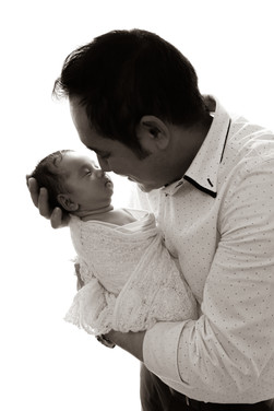 a father eskimo kissing with his newborn son, both dressed in white