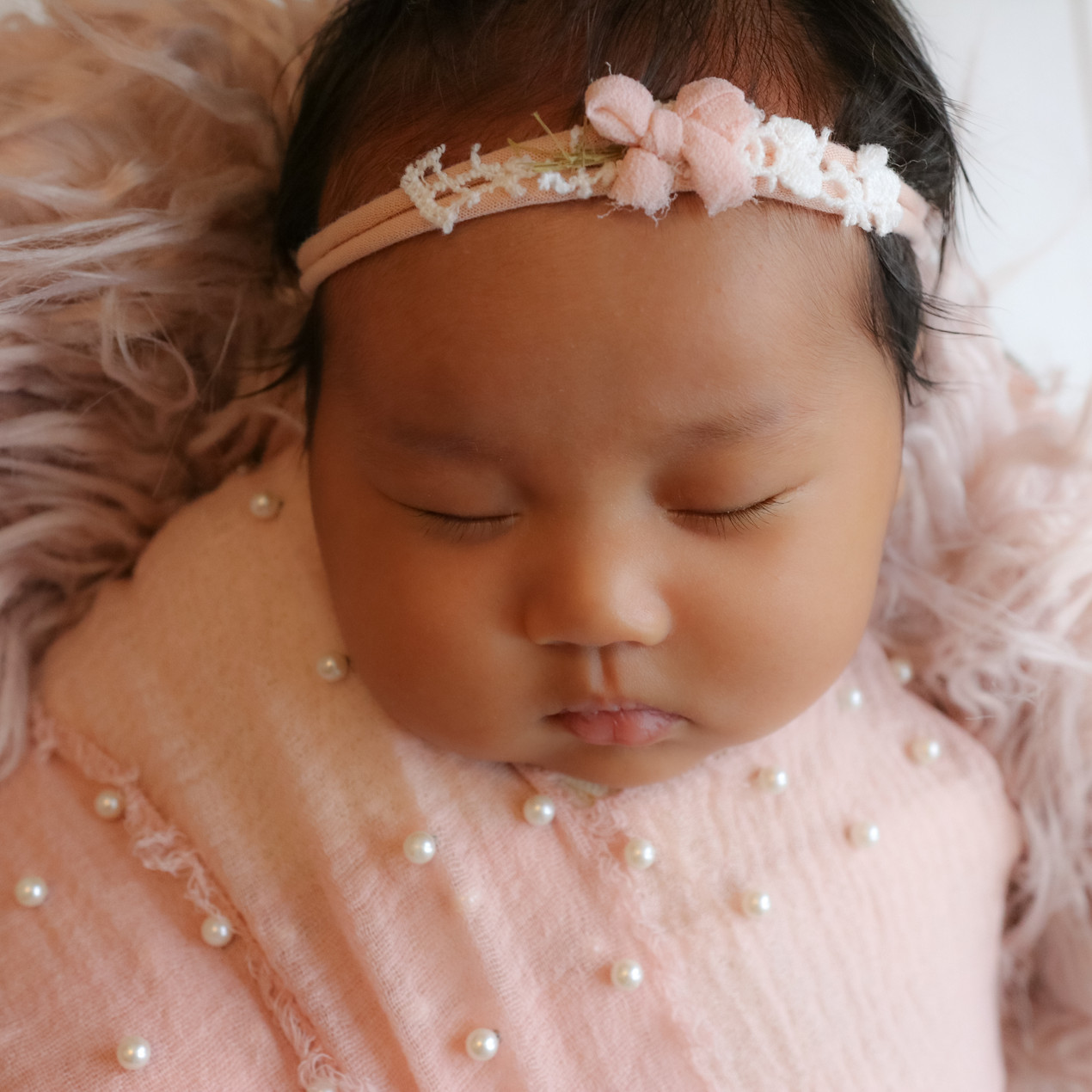 sleeping newborn girl wearing pink headband and wrap with peals