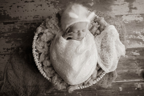 sleeping newborn with hand on cheek wearing a white bear bonnet and wrapped in white lying in wicker basket