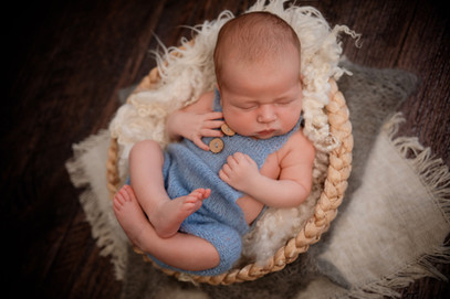 adorable sleeping newborn wearing a blue romper, curled up in a basket