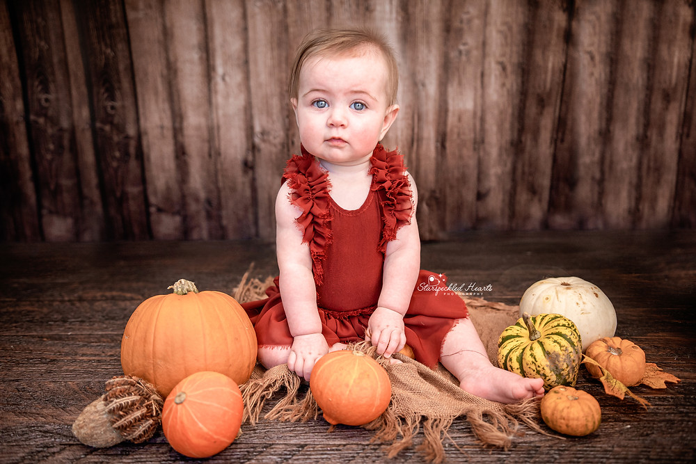 beautiful baby girl surrounded by pumpkins sitting on a dark wooden floor wearing a red dress