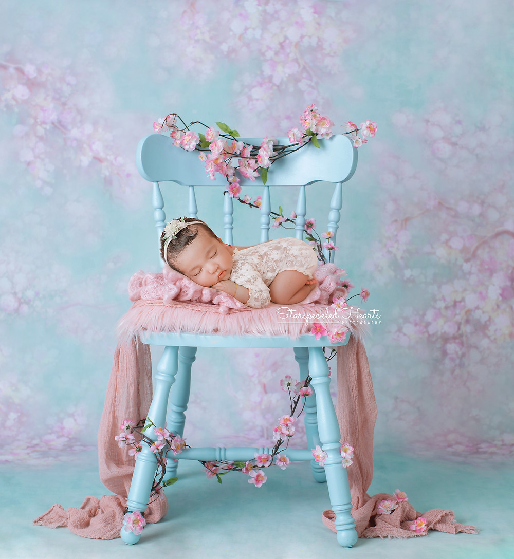 sleeping newborn baby girl laying on her tummy on a blue chair with pink cherry blossoms wound around it for her newborn photography session with starspeckled hearts photography in aldershot, hampshire
