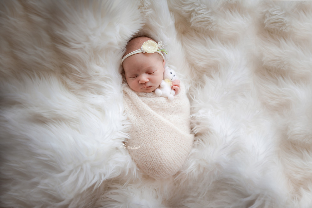 cute newborn girl wrapped in white, lying on a fluffy white rug