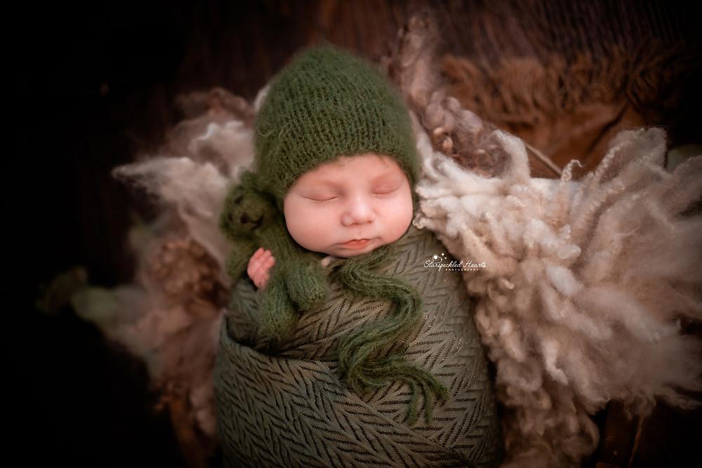 sleeping newborn wrapped in a green swaddle, lying in a wooden bowl cuddling a green teddy