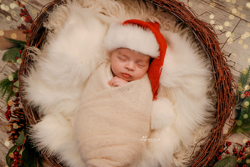 newborn baby christmas photo of baby boy wearing a santa hat, wrapped in white