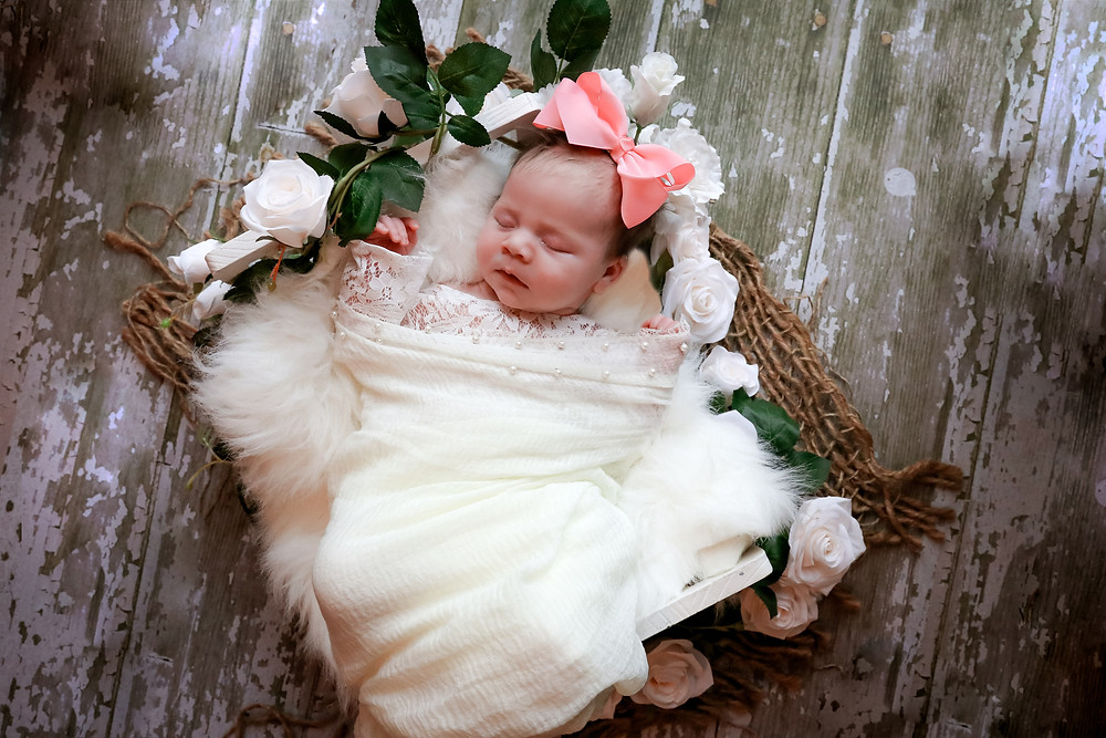 sleeping newborn with large pink bow laying in bed