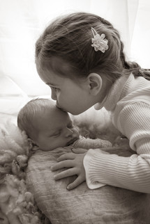 newborn boy swaddled and laying in a basket with toddler girl with braids sitting over him, giving him a kiss on his forehead