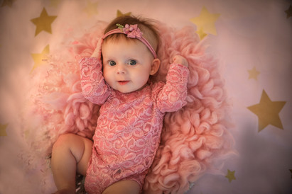 smiling baby girl wearing a pink romper, laying on a pink fluffy bed with gold stars around her