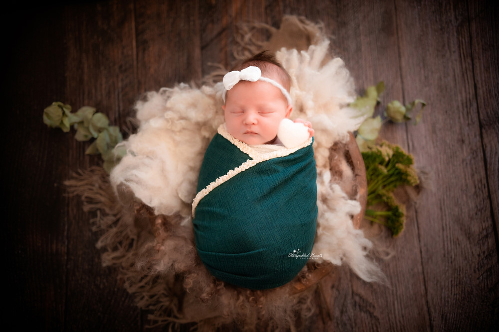 sleeping newborn baby swaddled with a teal wrap