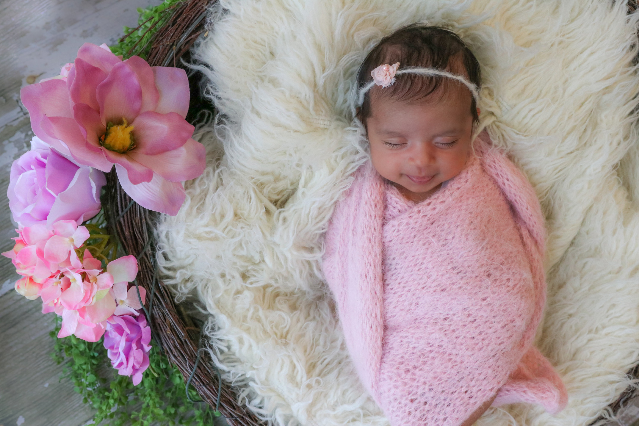 sleeping and smiling newborn girl wrapped in pink and laying in flower basket