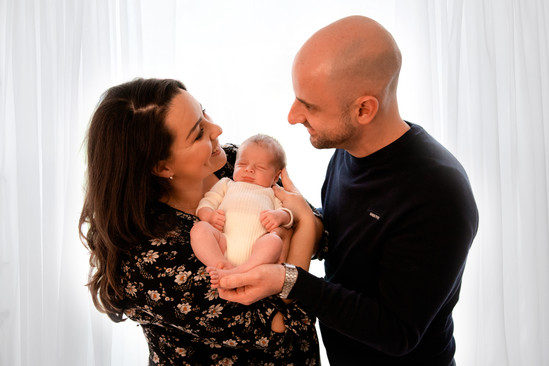 a beautiful family of 3, looking at each other and smiling with mum and dad wearing black and baby in white