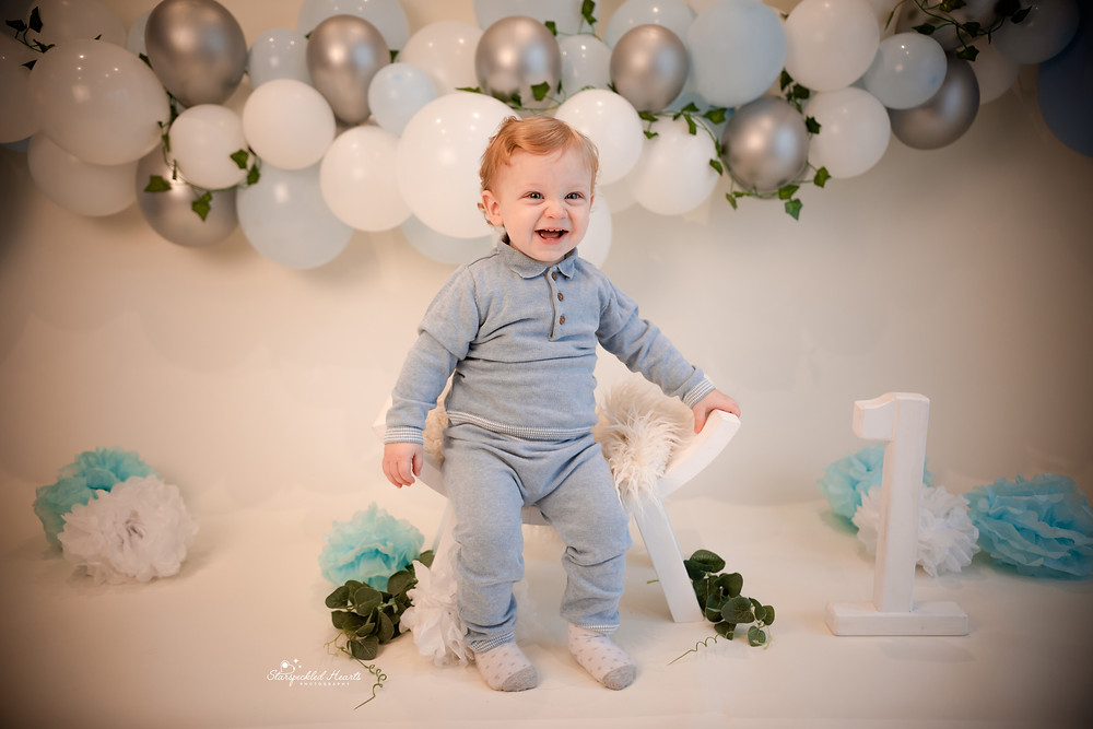 adorable baby boy with a big smile on his face sitting on a curved stool in front of a large balloon garland for his cake smash and splash session in aldershot, hampshire