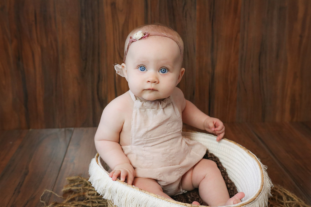 gorgeous baby girl with big blue eyes wearing a pink romper and matching headband, sitting in a wicker basket on a dark brown wooden background