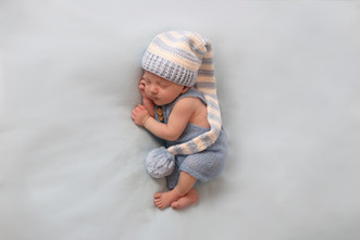 sleeping newborn baby wearing a blue and white stiped sleepy cap and blue romper on a blue background