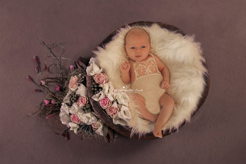 gorgeous baby girl wearing a lacy romper, lying in a white wicker basket surrounded by flowers and greenery