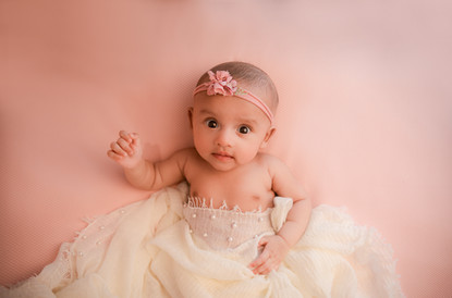 adorable baby girl lying on a pink backdrop for her 2 month milestone session with starspeckled hearts photography