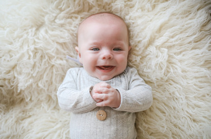 smiling baby boy lying on a white fluffy rug, wearing a grey romper