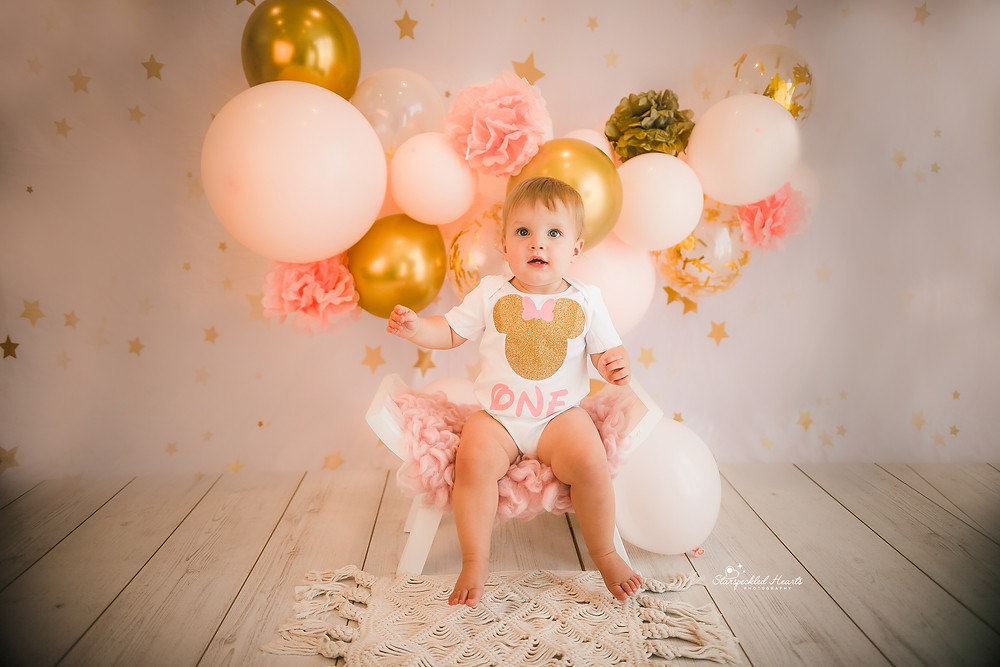 baby girl sitting on a curved stool in front of a large balloon garland with pink and gold balloons